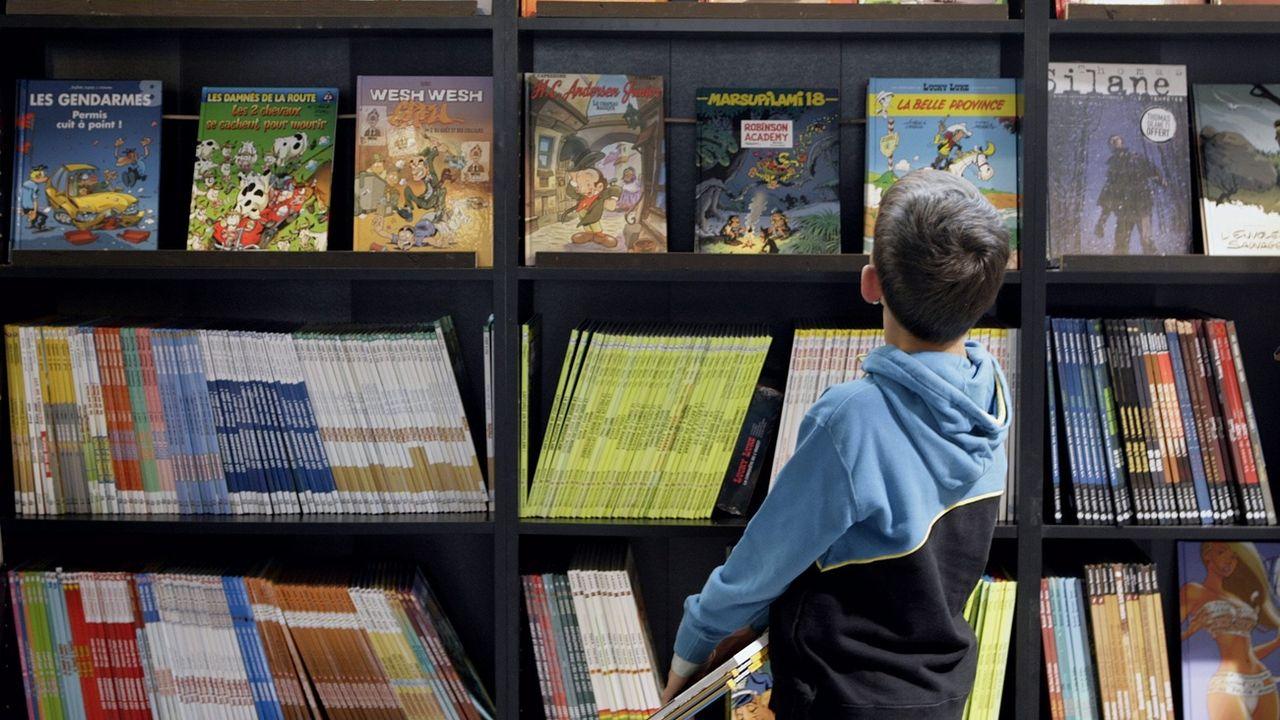Un enfant regarde les albums exposés dans la Grande Librairie, lors du BD-FIL 2006 Festival International de BD Lausanne, le 9 septembre 2006 à Lausanne. [Salvatore Di Nolfi - Keystone]