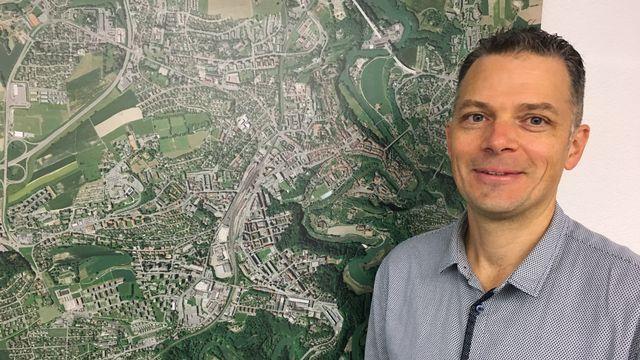 Raphaël Casazza, ingénieur EPFL en environnement, devant la carte de Fribourg. [Jean de Preux - RTS]