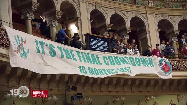 Des jeunes activistes pour le climat ont infiltré la salle du Conseil national avec une grande banderole. [RTS]
