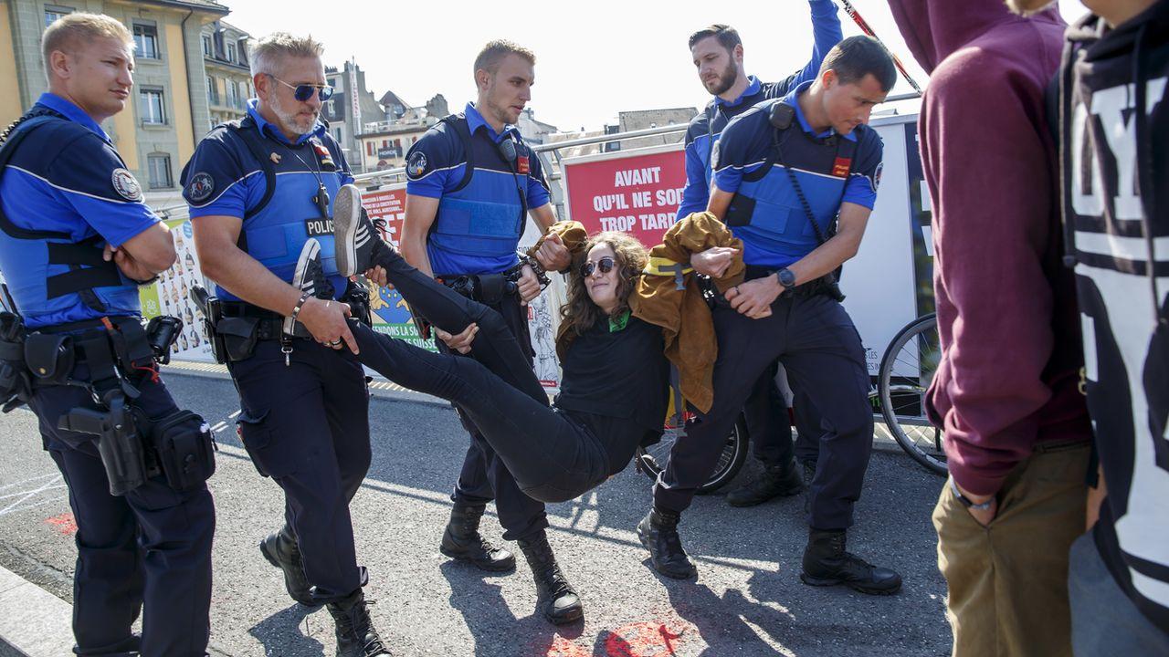 Une activiste évacuée par la police sur le pont Bessières de Lausanne. [Salvatore Di Nolfi - Keystone]