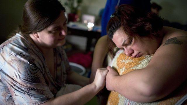 Une Doula tenant les mains d'une femme hongroise ayant choisi une naissance à la maison [Bea Kallos - EPA/Keystone]