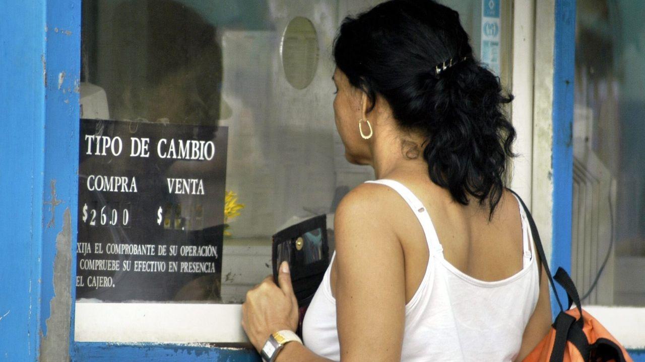 Une femme devant une banque à Cuba. [EPA/Alejandro Ernesto - Keystone]