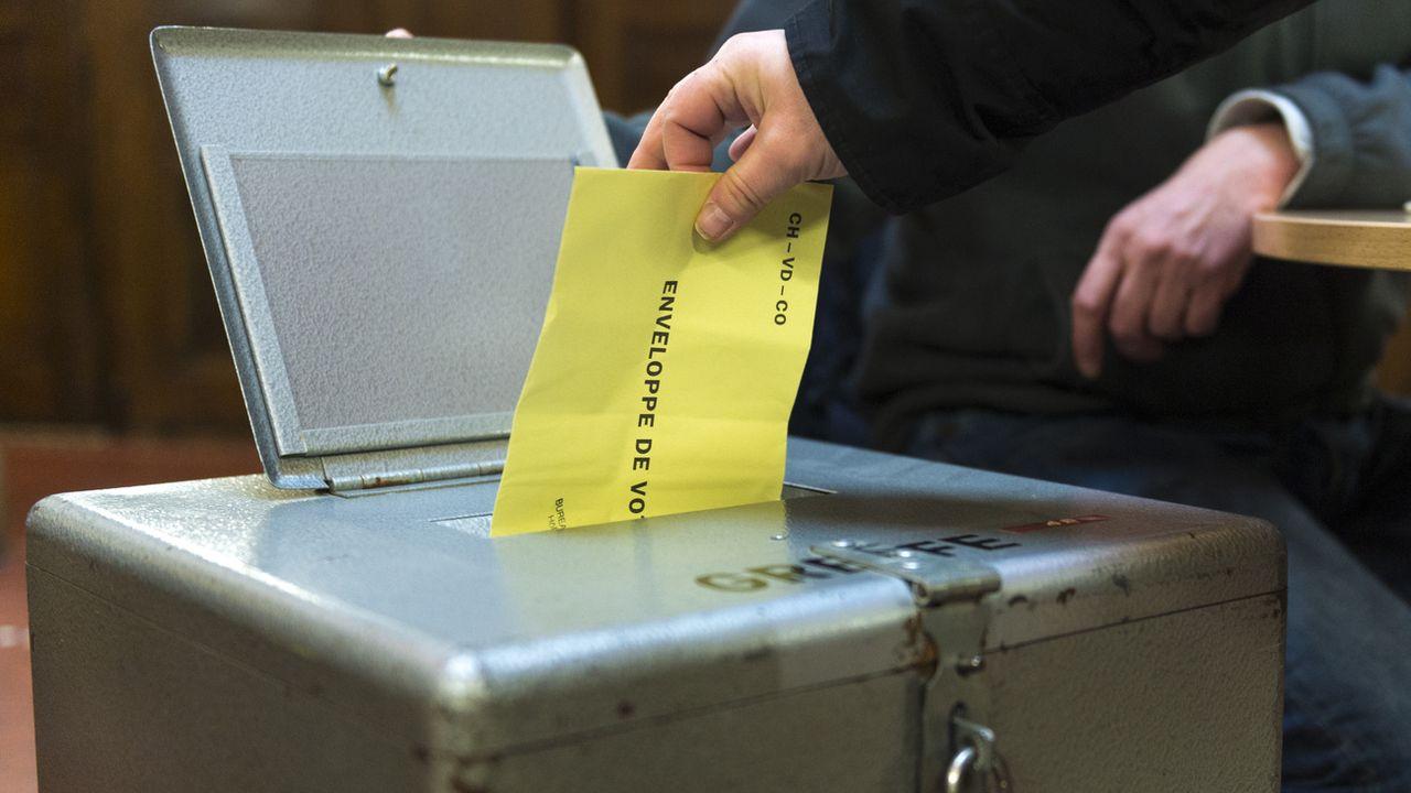 Une enveloppe de vote glissée dans l'urne. [Gabriel Monnet - Keystone]