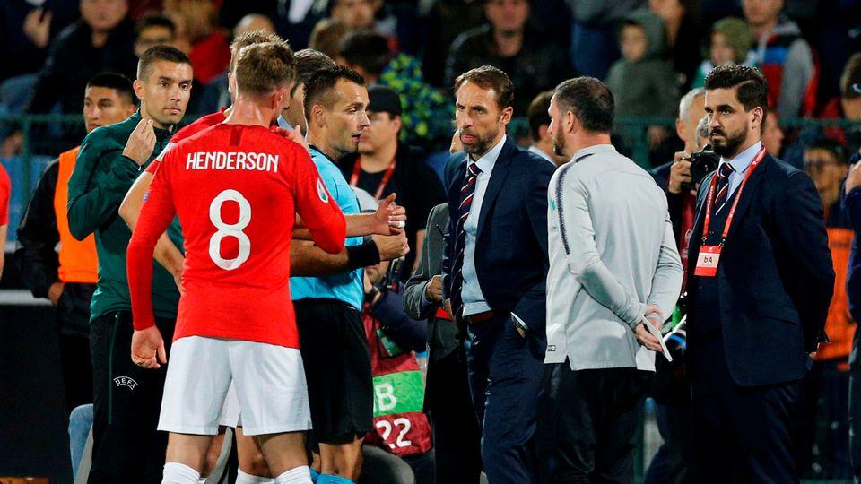 Jordan Henderson et Gareth Southgate, le sélectionneur de l'Angleterre, discutent avec l'arbitre Ivan Bebek dans un stade où des cris et chants racistes ont tristement rythmé leur soirée. [ANTONIN UZUNOV - REUTERS]