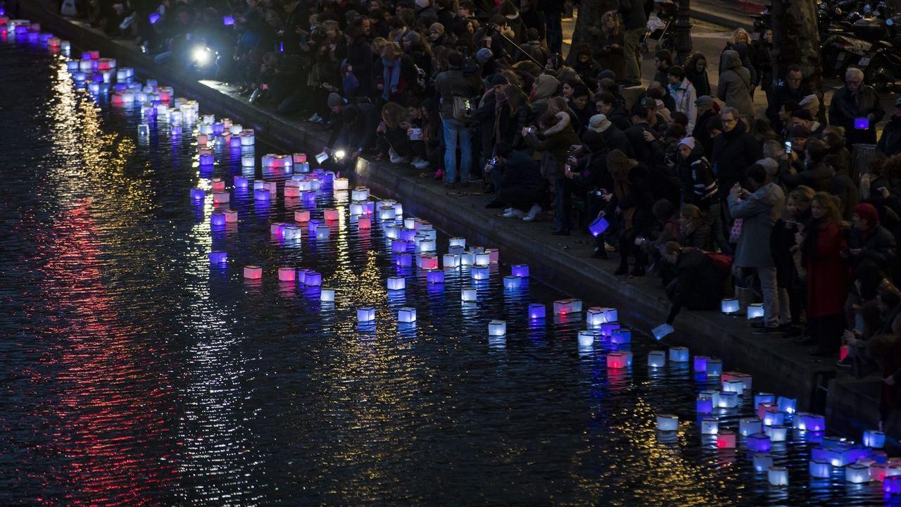 Un an après les attentats de Paris, des gens placent des lanternes colorées dans le Canal Saint-Martin, non loin de la Place de la République, le 13 novembre 2016. [Ian Langsdon - Keystone/epa]