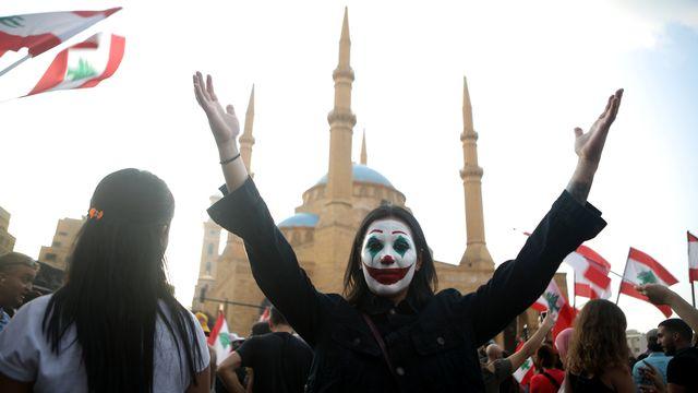 Une manifestante libanaise s'est peint le visage pour ressembler au Joker. Beyrouth, le 19 octobre 2019. [Patrick Baz - afp]