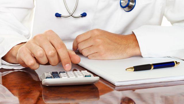Gros plan sur un médecin utilisant une calculatrice. [ginasanders - Depositphotos]