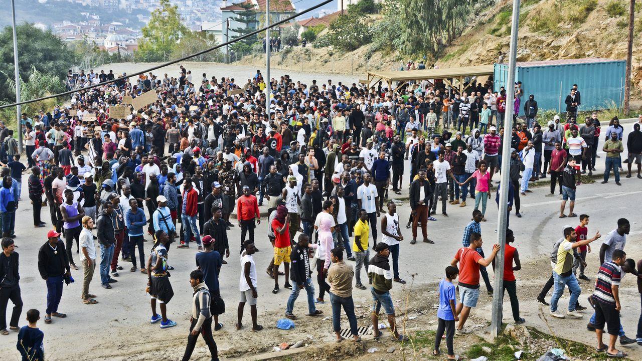 Des réfugiés et des migrants protestent à l'extérieur d'un camp surpeuplé sur l'île grecque de Samos. [Michael Svarnias - Keystone/AP Photo]