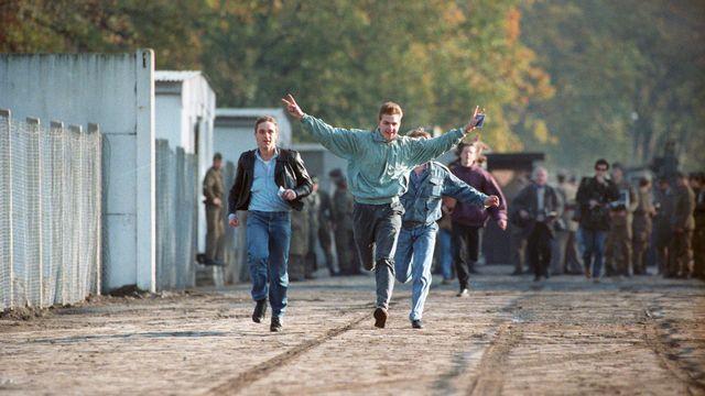 Trois jeunes de Berlin-Est traversent la frontière vers Berlin-Ouest. [Keystone/DPA]