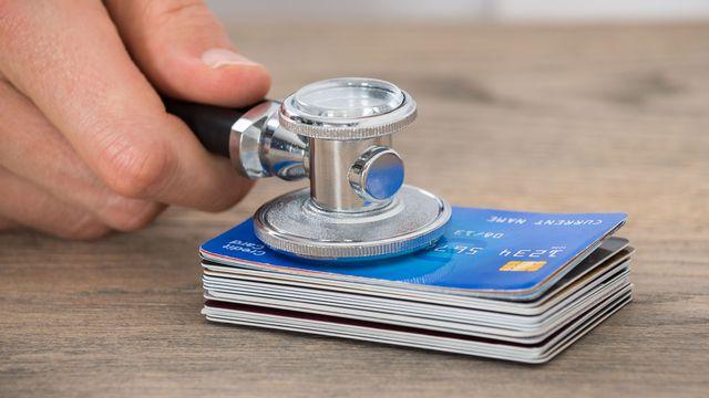 Un stéthoscope ausculte une pile de cartes de crédit. [AndreyPopov - Depositphotos]