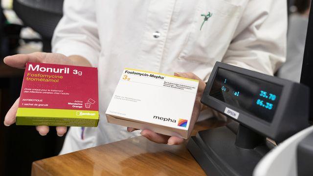 Une pharmacienne présente deux boîtes d'antibiotiques couramment utilisés pour soigner les infections urinaires. [Gaetan Bally - Keystone]