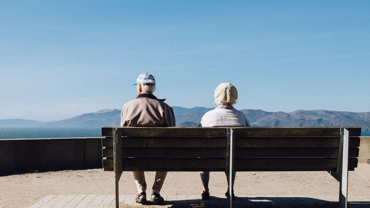 Un couple de seniors assis sur un banc regardent les montagnes. [Matthew Bennett - Unsplash]