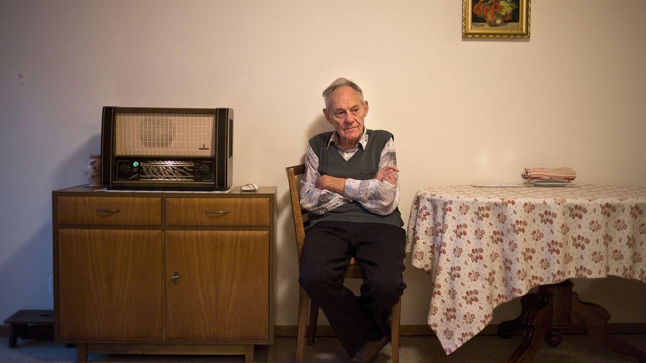 Un homme dans son appartement en Suisse. [Martin Ruetschi - Keystone]