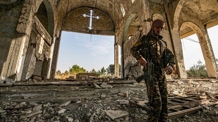 Membre des Gardiens du Khabour dans les ruines d'une église assyrienne à Tal Tamr, 15.11.2019.