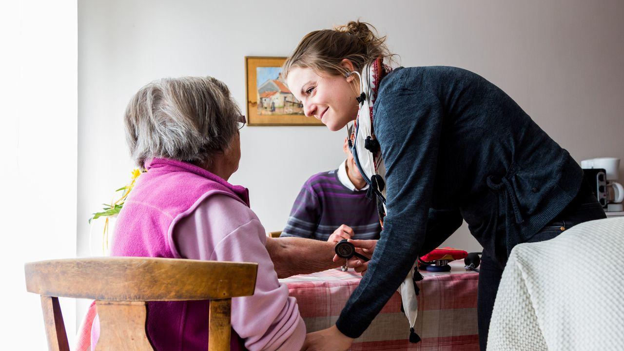 Une aide à domicile s'entretient avec une patiente. [Garo Phanie - afp]