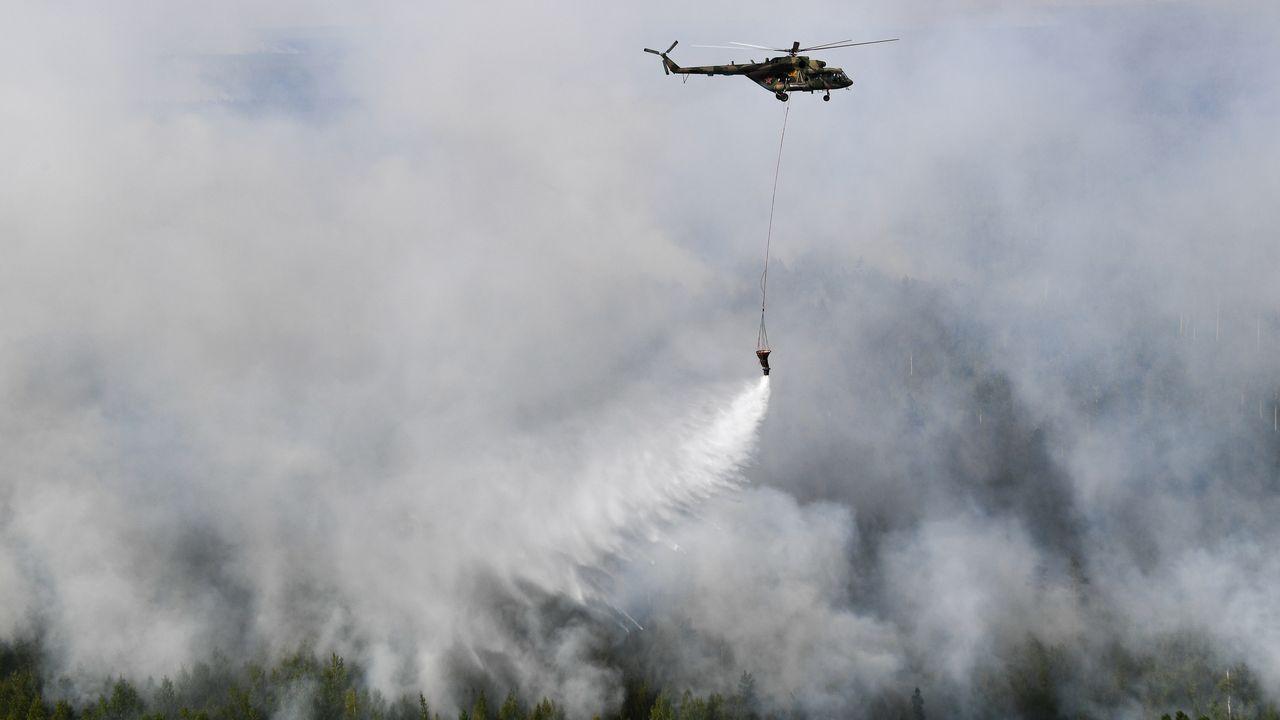 Un hélicoptère des forces russes déverse de l'eau sur les feux de forêt qui se sont déclarés dans le district de Boguchansky, en Sibérie, en août 2019. [Alexandr Kryazhev - Sputnik]