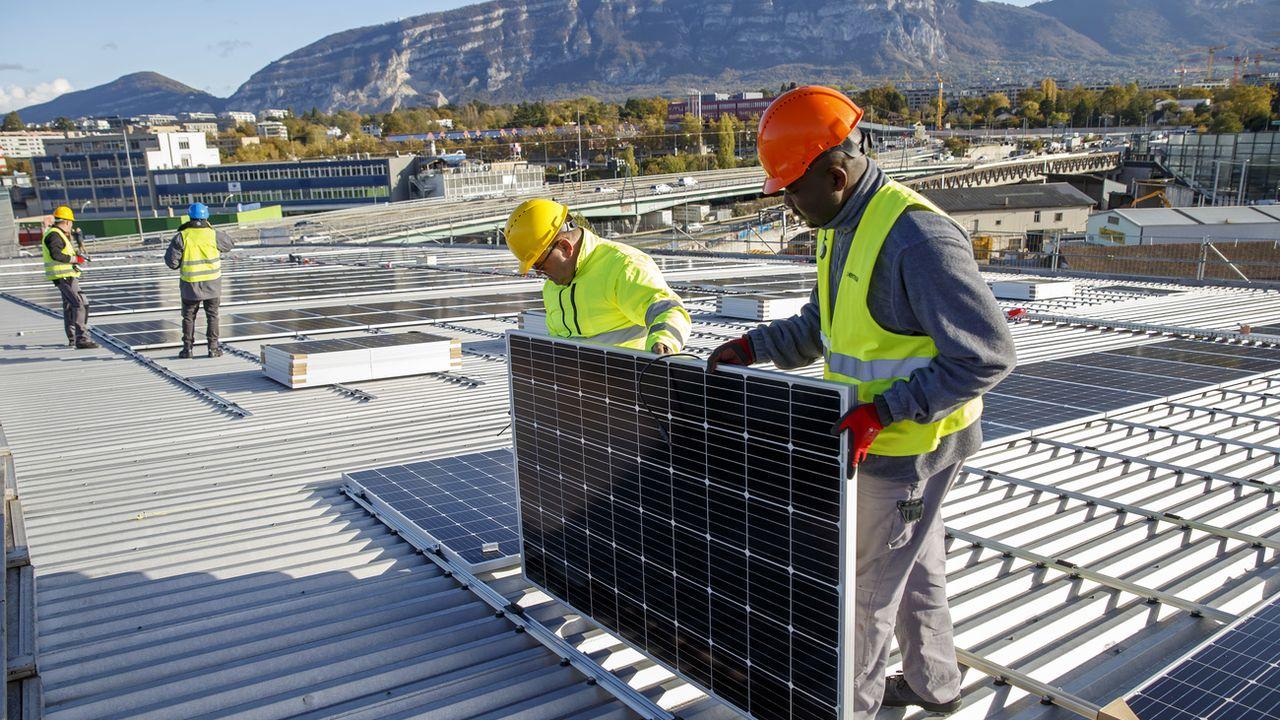 Des ouvriers posent des panneaux solaires sur le toit du stade de Genève, le 12 novembre 2019. [Salvatore Di Nolfi - Keystone]