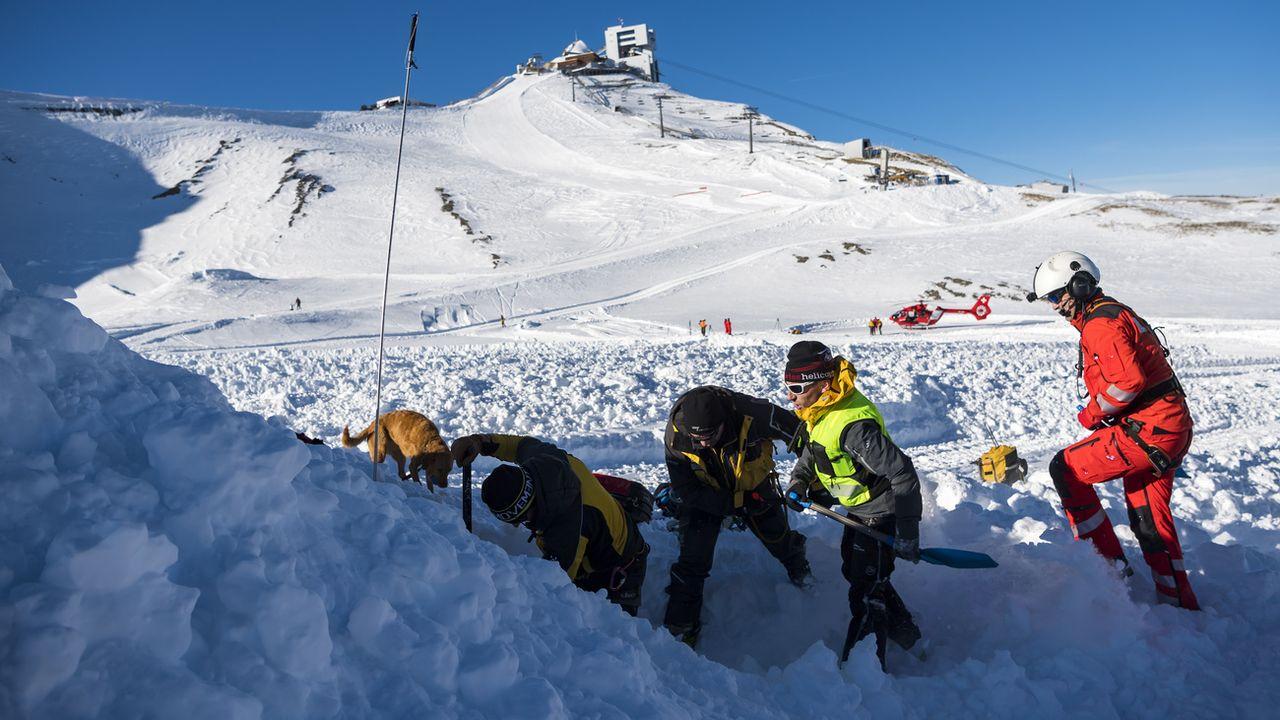 Des secouristes et un chien cherchent une victime lors d'un exercice de sauvetage. [Jean-Christophe Bott - Keystone]