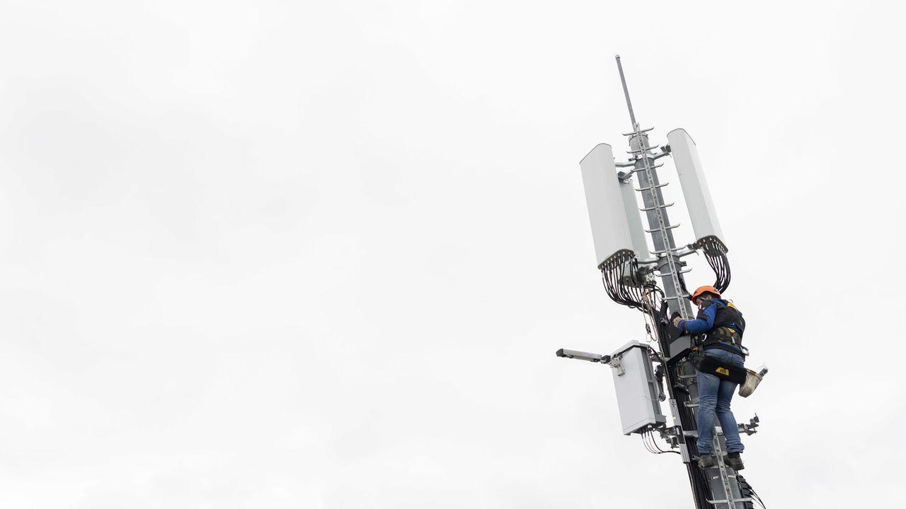 Un employé de l'entreprise Axians installe une antenne 5G à Chêne-Bougeries, en avril 2019. [Martial Trezzini - Keystone]