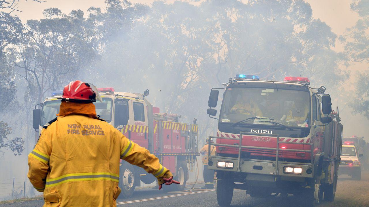 Des pompiers cherchent à sécuriser des zones résidentielles alors que des incendies font rage sur la Côte Centrale, à environ 100 kilomètres de Sydney. [Saeed Kahn - AP Photo]