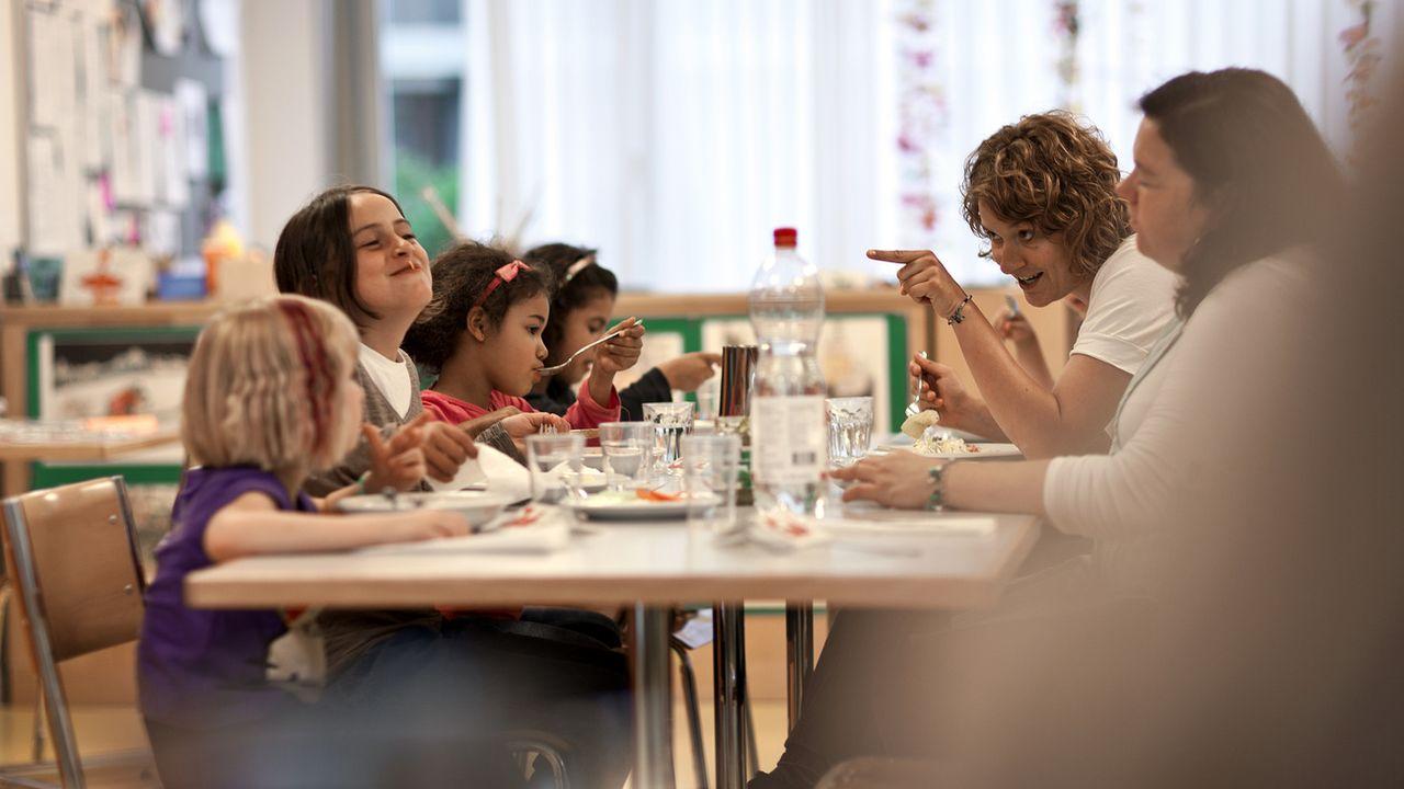 Des enfants et des éducatrices partagent un repas à Zurich. [Gaetan Bally - Keystone]