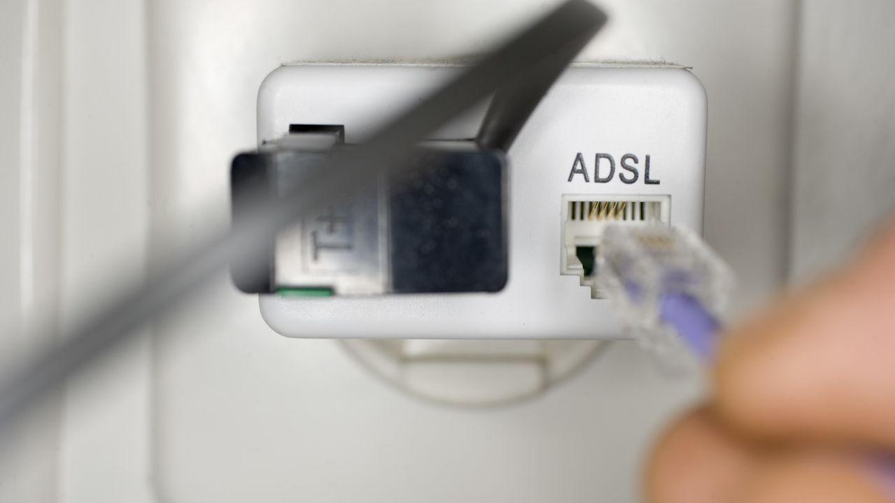 Un usager branche une prise ADSL dans la prise du téléphone fixe. [Martin Ruetschi - Keystone]