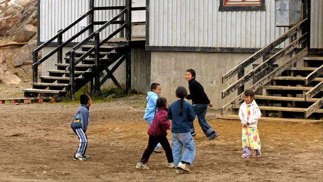 Enfants de l'éthnie Inuit jouant devant une maison en bois dans le village de Tiniteqilaaq. [PHILIPPE ROY / Aurimages - AFP]