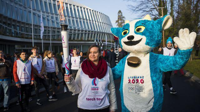 Yodli, la mascotte des JOJ 2020, pose en compagnie d'une relayeuse de la flamme olympique. [Jean-Christophe Bott - Keystone]