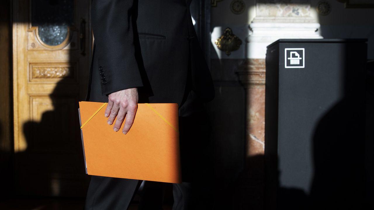 Un parlementaire portant un dossier dans les pas perdus à Berne. [Peter Klaunzer - Keystone]