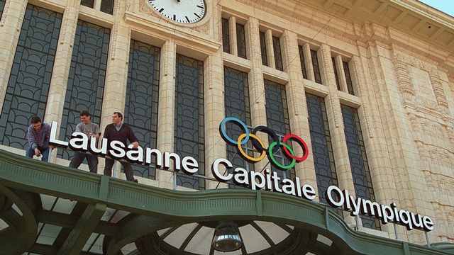 """Des ouvriers installent le panneau lumineux """"Lausanne capitale olympique"""" au-dessus de l'entree principale de la gare de Lausanne, en 1997. [Fabrice Coffrini - Keystone]"""