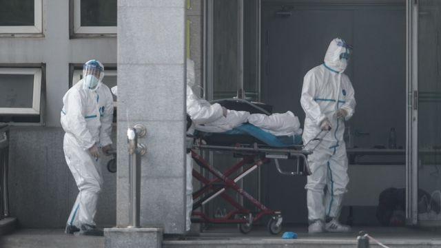 Du personnel médical transporte un patient atteint du coronavirus dans un hôpital de Wuhan. [Keystone/EPA]