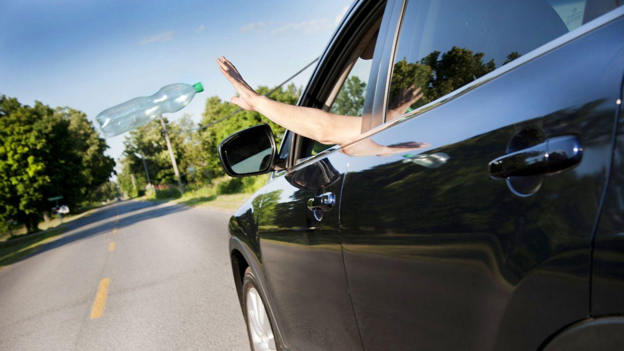 Une personne jette un déchet par la fenêtre de sa voiture. [Justek16 - Depositphotos]