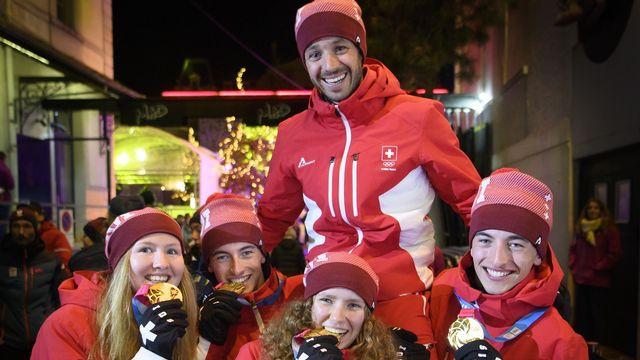 Les médaillés d'or en ski alpinisme Caroline Ulrich, Thomas Bussard, Thibe Deseyn et Robin Bussard portent leur coach Malik Fatnassi, le 14 janvier 2020. [Laurent Gillieron - Keystone]