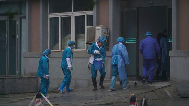 Le personnel du Wuhan Medical Treatment Center nettoie l'entrée du bâtiment pour éviter les cas de contamination par le nouveau coronavirus chinois. [Dake Kang - Keystone/Dake Kang]