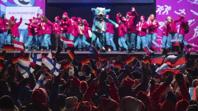 Yodli, la mascotte des JOJ, dansent au milieu de jeunes athlètes. [Keystone]