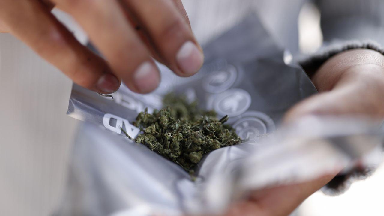 Un consommateur prépare son mélange de cannabis en vue de fumer un joint. [Rebecca Blackwell - AP/Keystone]
