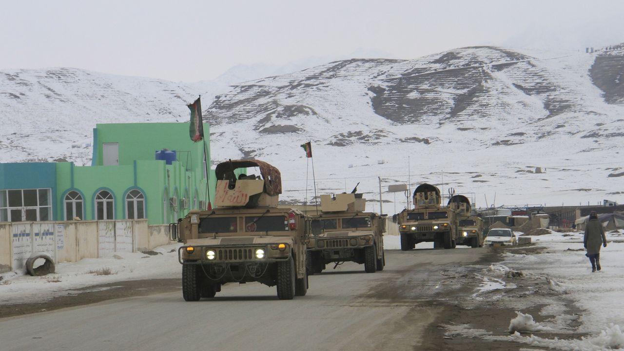 Des soldats afghans se déplacent sur le lieu du crash. [Sayed Mustafa - Keystone ]