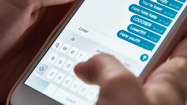Cyber-harcèlement: messages offensants sur un smartphone. [VadimVasenin - Depositphotos]