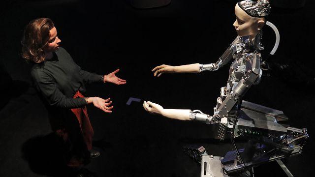 Une femme interagit avec un robot [Frank Augstein - Keystone]