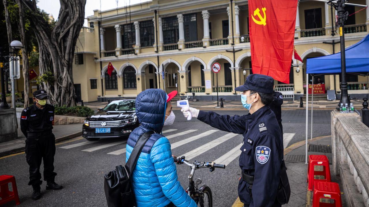 Des gardes de sécurité contrôlent la températures des passants, ce 10 février 2020 à Guangzhou, en Chine. [Keystone]
