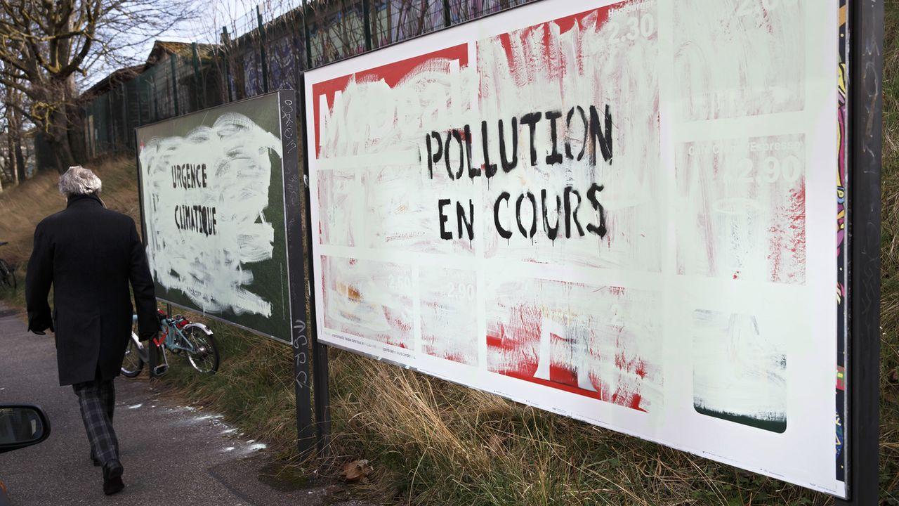 """Une personne passe devant des affiches publicitaires recouvertes de peinture avec le message """"Pollution en cours"""", Genève le 12 mars 2019. [Salvatore Di Nolfi - Keystone]"""