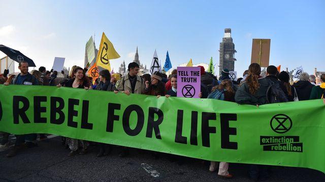"""Des activistes du groupe """"Extinction Rebellion"""" en marche sur le Westminster Bridge à Londres en 2018. [Alberto Pezzali / NurPhoto - AFP]"""