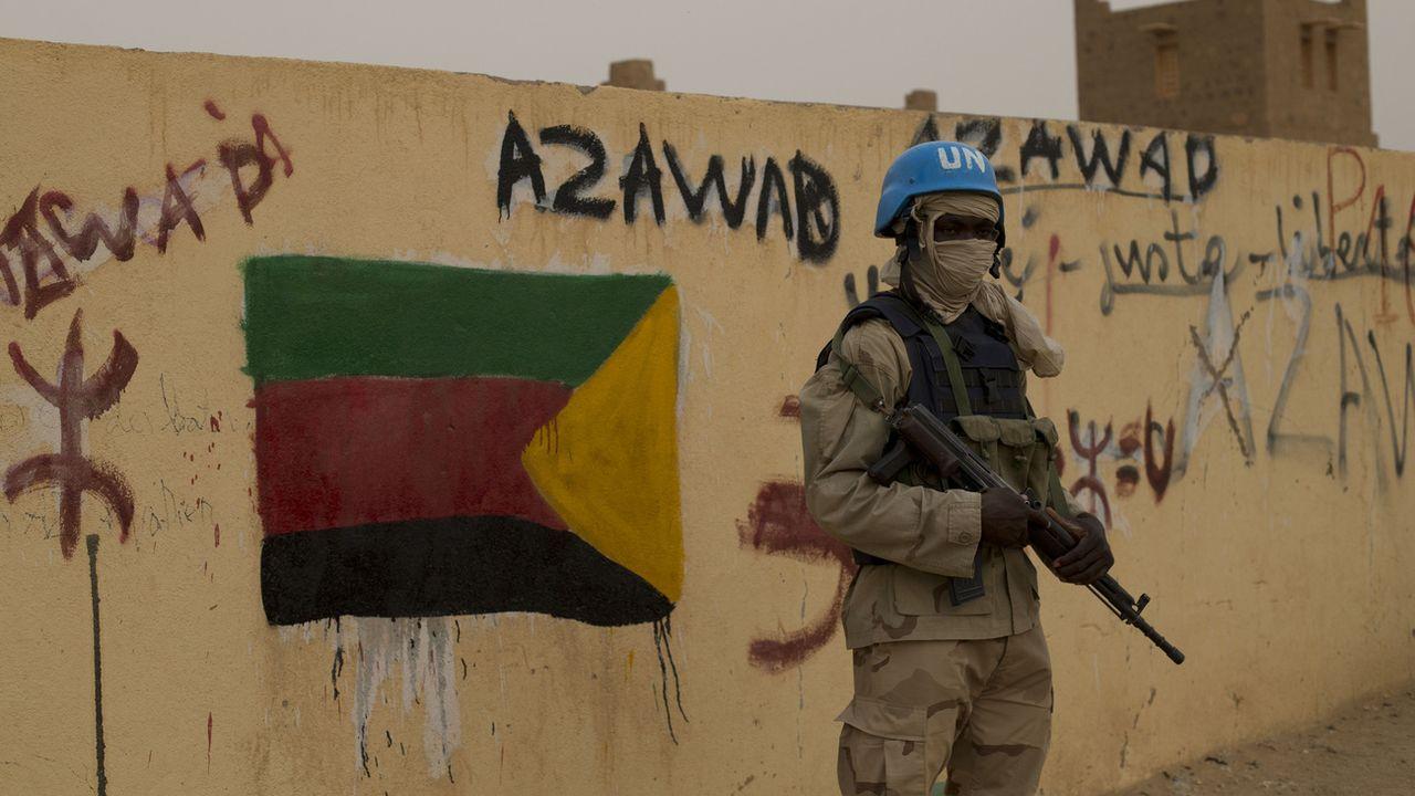 Un soldat de la mission de l'ONU au Mali à Kidal en 2013, devant une slogan de soutien à l'Azawad (CMA), alliance à dominante touareg d'anciens groupes armés rebelles. [AP Photo/Rebecca Blackwell - Keystone]