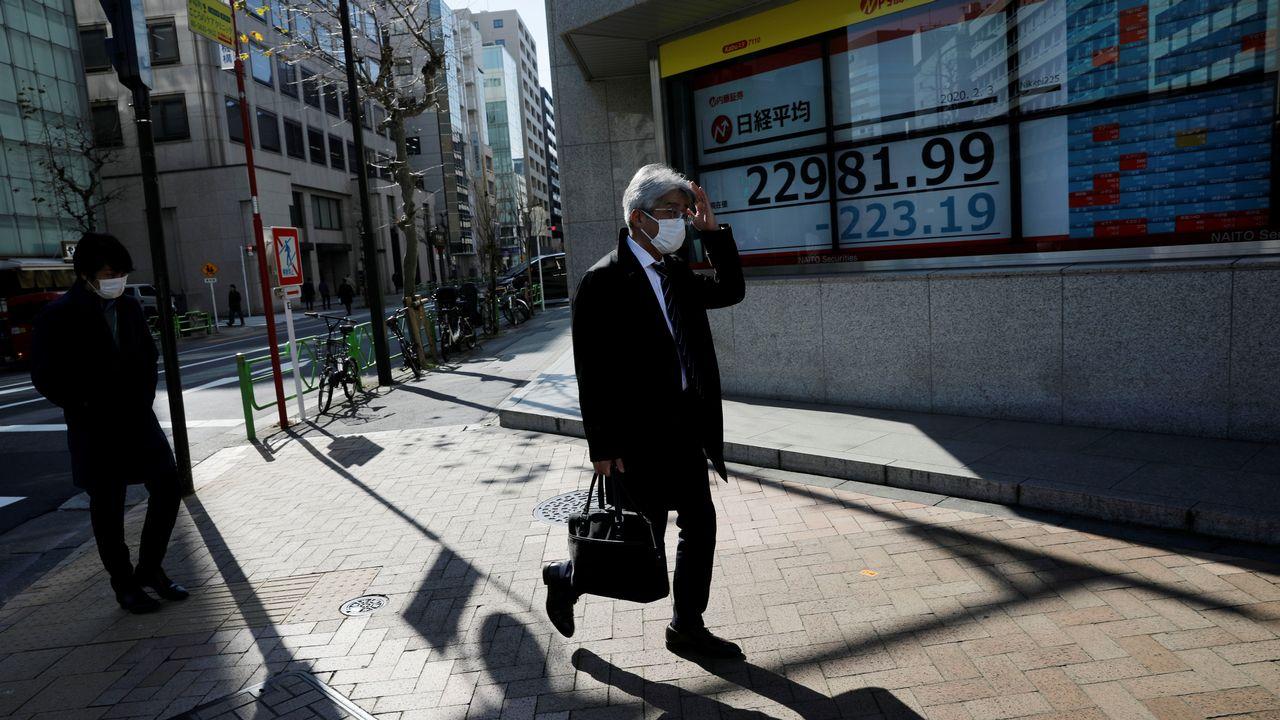 Un homme portant un masque passe devant un écran affichant la valeur de l'indice Nikkei. Tokyo, le 3 février 2020. [Kim Kyung-Hoon - Reuters]