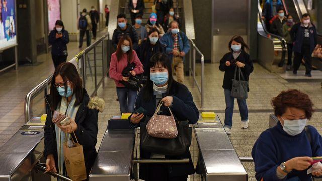 Pendulaires portant des masques dans une station de métro à Hong Kong suite à l'émergence du coronavirus. [MIGUEL CANDELA - EPA / Keystone]