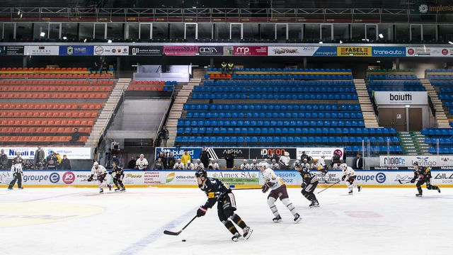Les joueurs fribourgeois et genevois se sont affrontés dans une patinoire vide samedi. [Adrien Perritaz - Keystone]
