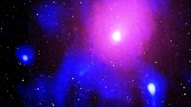 Ce qui reste de l'explosion la plus formidable de l'Univers, due à un trou noir supermassif, dans l'amas d'Ophiuchus. En rose, les rayons-X; en bleu, les ondes radio; en blanc, l'infrarouge. [X-ray: Chandra: NASA/CXC/NRL/S. Giacintucci, et al., XMM-Newton: ESA/XMM-Newton - Radio: NCRA/TIFR/GMRT; Infrared: 2MASS/UMass/IPAC-Caltech/NASA/NSF]