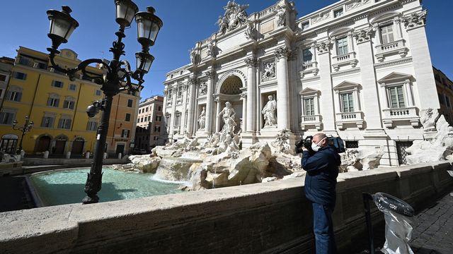 Un journaliste filmant la Fontaine de Trévi désertée suite aux mesures mises en place par l'Italie pour réduire la propagation du coronavirus. [Vincenzo Pinto - AFP]