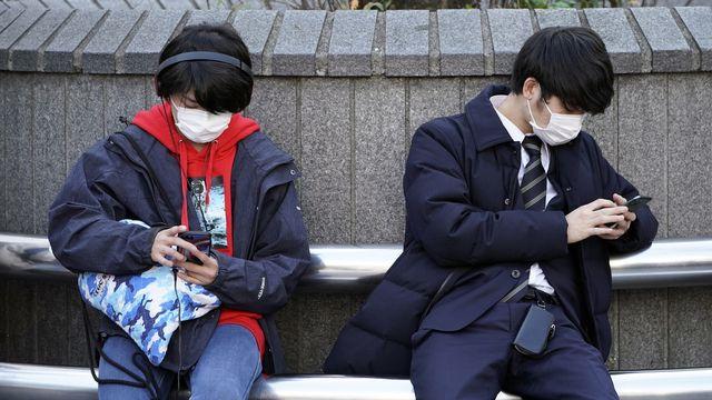 De jeunes hommes portant des masques dans le district de Shibuya, à Tokyo, le 3 février 2020. [Franck Robichon / EPA - Keystone]