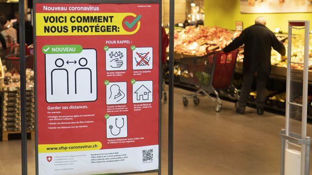 Une affiche de prévention à l'entrée d'un supermarché. [Laurent Gillieron - Keystone]